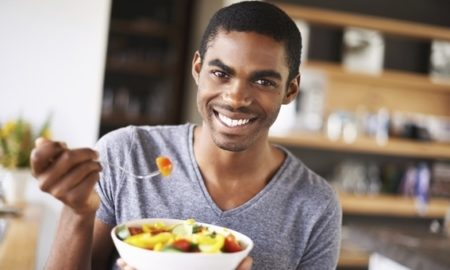 Indoor shot of a gorgeous young black man showing off his fruit salad