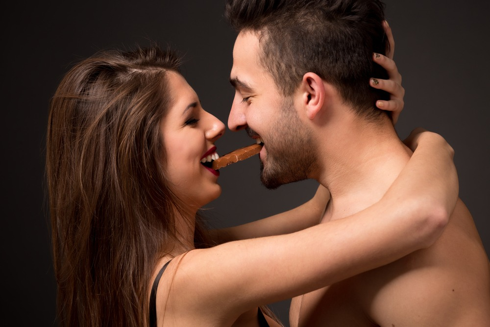 Passionate couple hugging and holding chocolate in their mouths