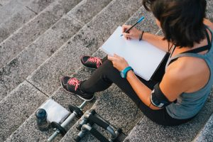 woman writing down fitness progress sitting on stairs