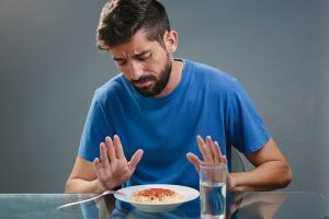 man with no appetite pushing away pasta