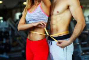 healthy fit man and woman in gym measuring waists