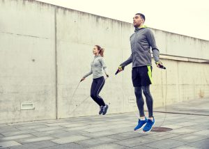 man and woman doing cardio with jumping rope