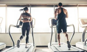 man and woman doing cardio by running on treadmill