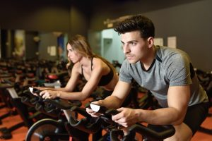 man and woman doing cardio on stationary bike
