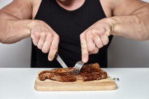man eating steak, protein
