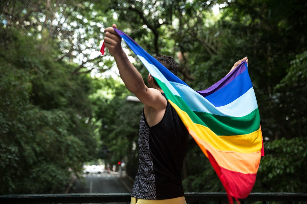 gay man holding rainbow equality flag, lgbtq