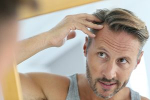 middle aged man looking at thinning hair