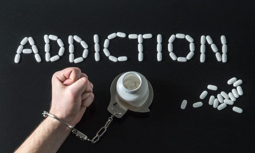 drug addiction hand cuffed to pill bottle