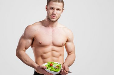 healthy man holding a bowl of veggies