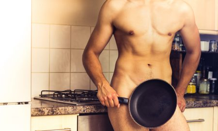 naked man holding a frying pan