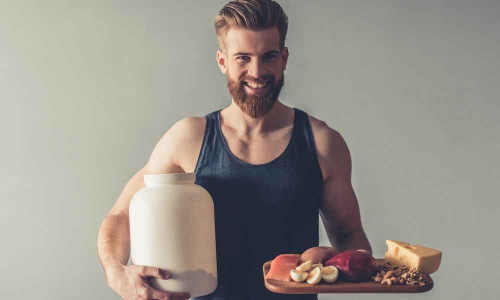 a guy holding foods that are rich in protein