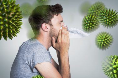 man with cold virus sneezing