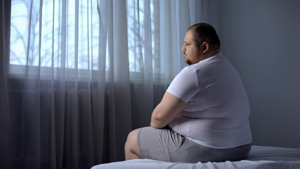 sad fat man sits on bed