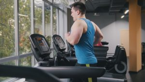 overweight man running on treadmill