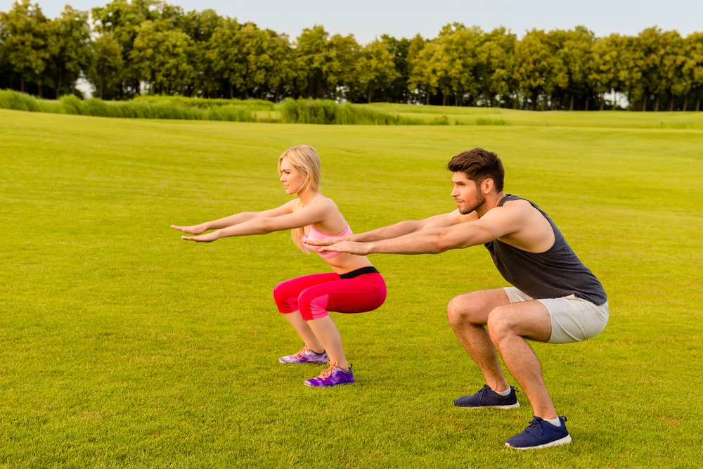 couple doing air squat outdoors